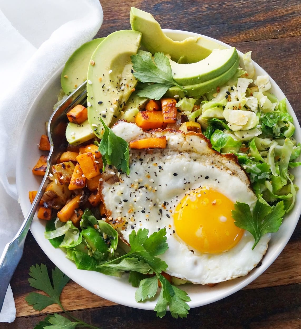 Top down of a white Whole30 breakfast bowl on a wooden board filled with diced and roasted potatoes, sliced Brussels sprouts, a fried egg, and sliced avocado.