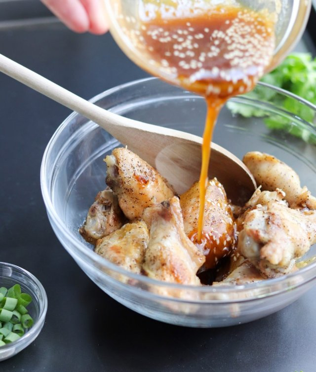 Process cooking shot of the cooked chicken wings in a glass bowl being drizzled with the honey sriracha sauce.