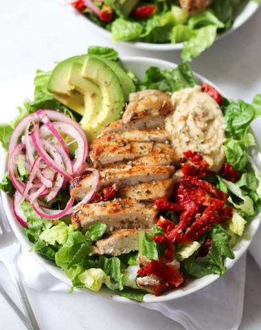 Close up of the finished recipe. A white bowl is filled with chopped romaine lettuce, sundried tomatoes, hummus, sliced grilled chicken, avocado and pickled onions.