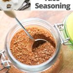 "Close up of taco seasoning in a small glass jar with the ingredients with the text ""Whole30, Keto Homemade Taco Seasoning"" for Pinterest."