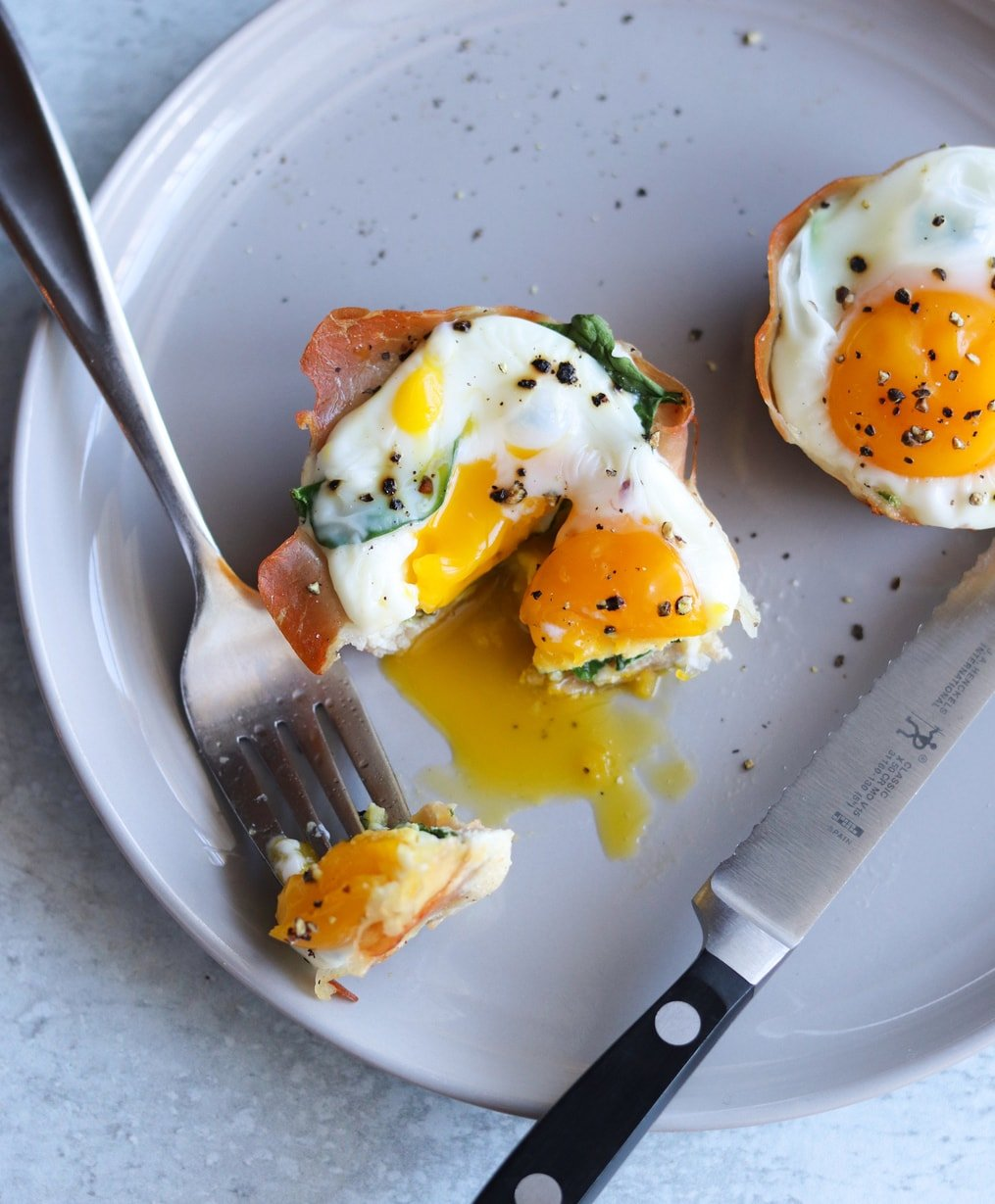 Plated prosciutto egg cups on a gray plate, with a fork and knife cutting into one and some of the runny yolk spilling out.