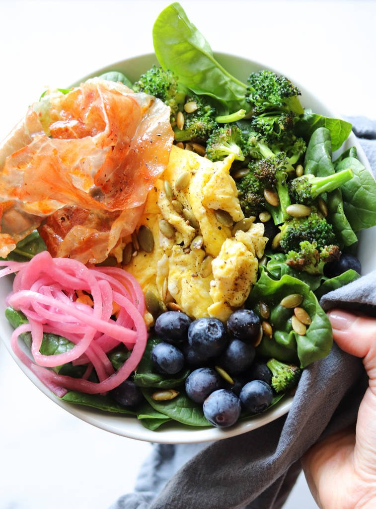 Top down of a hand holding a white breakfast bowl filled with spinach, scrambled eggs, prosciutto, broccoli, pickled onions, and blueberries.