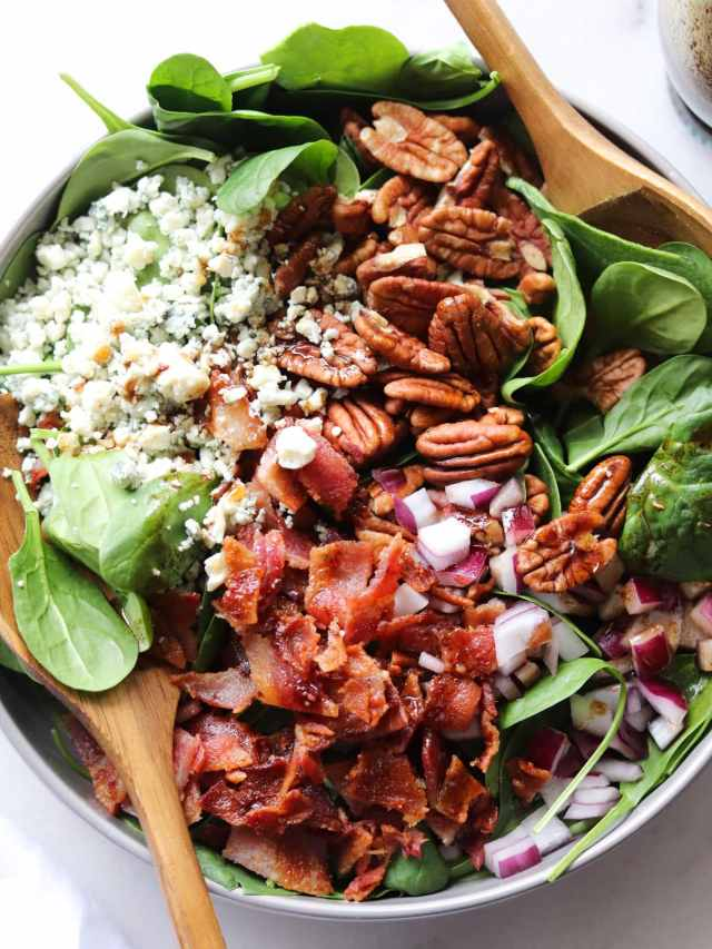 Close up of the salad topped with bacon, blue cheese, onion and pecans, serving in a gray bowl with two large wooden serving spoons.