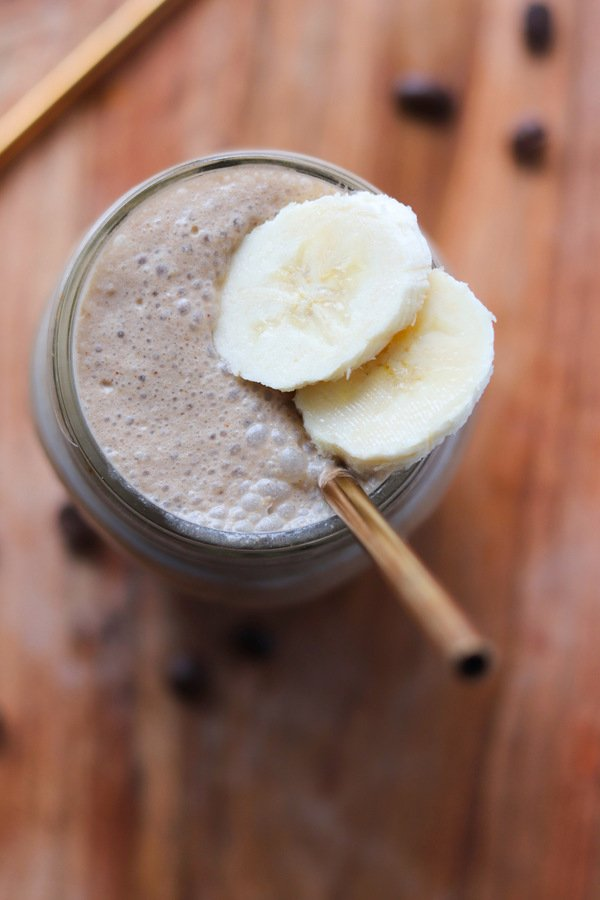 Close up top down of the finished smoothie in a mason jar, topped with sliced of banana and served with a gold straw.