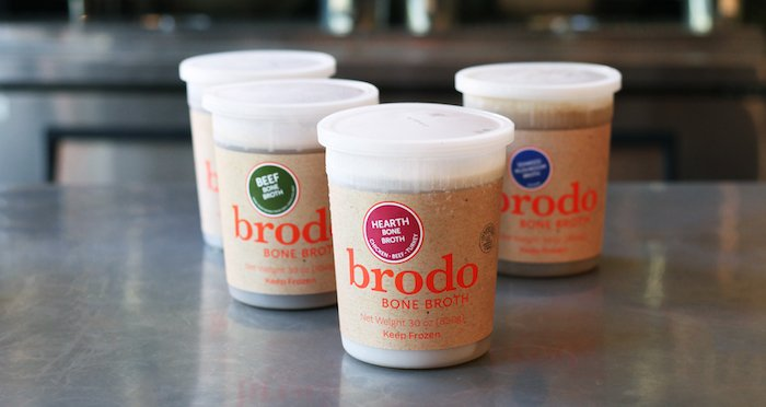 Four cups of Brodo bone broths on a table