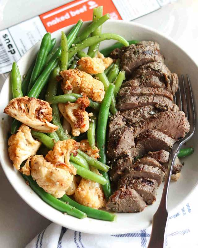 The Naked Beef Whole30 meal with sliced beef, cauliflower, and green beans, plated in a white bowl.