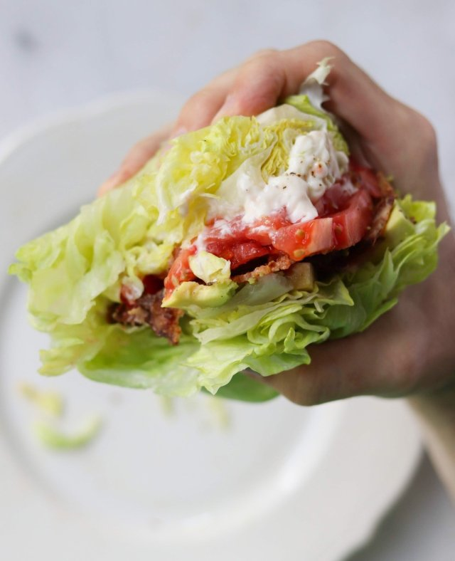 A hand holding the messy sandwich above a white plate with bites taken out of it.