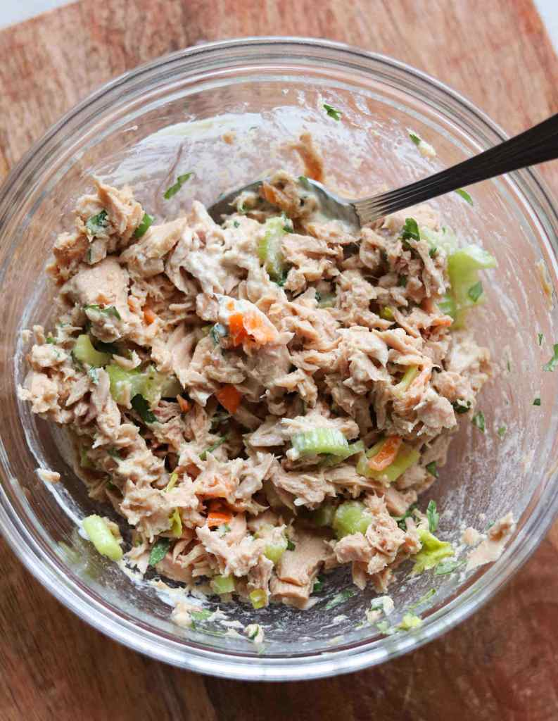 A glass bowl filled with tuna salad that's been mixed up.