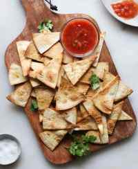 Tortilla chips on a brown cutting board with salsa.