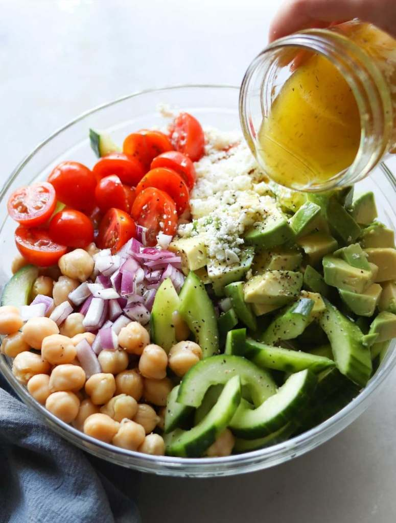 A Greek chickpea salad in a large glass dish with the Greek vinaigrette drizzled on top.