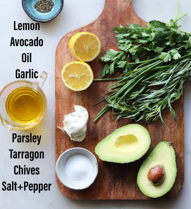A wooden cutting board on a white board with all the ingredients laid out: Lemon, Avocado, Oil, Garlic, Parsley, Tarragon, Chives, and salt and pepper.
