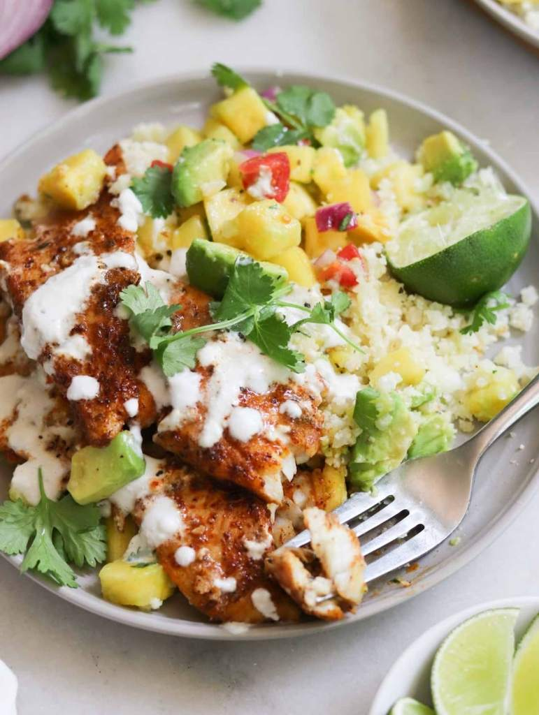 The finished blackened flounder, plated on a small gray dish and served with cauliflower rice, pineapple salsa, and chili-lime drizzle.