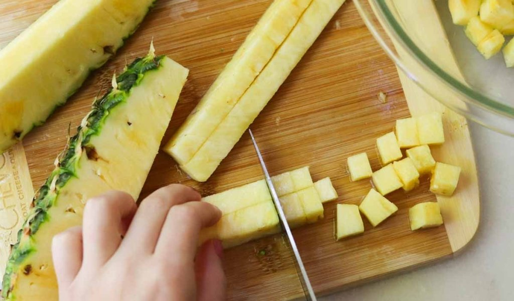 Two hands dicing pineapple on a wooden cutting board.