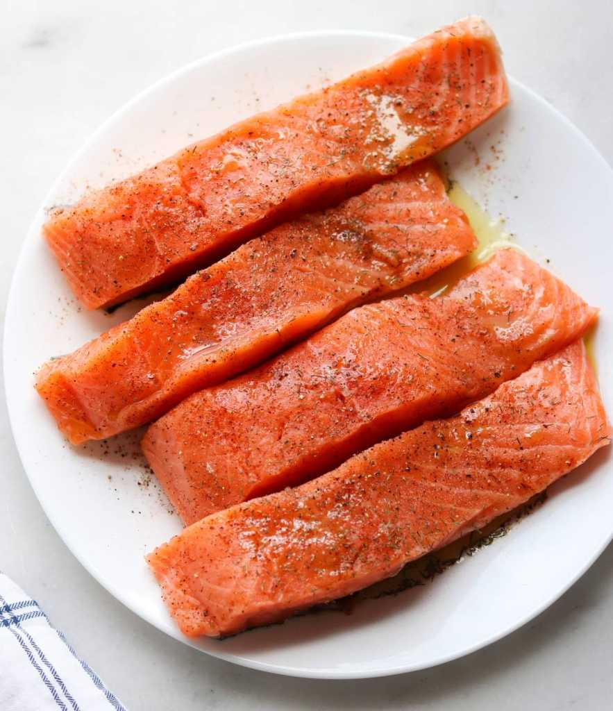 Raw marinated salmon fillets on a white plate.