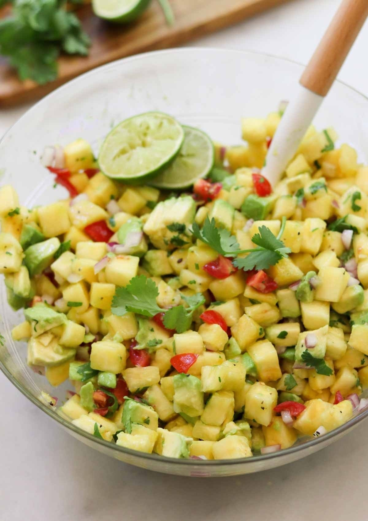 Close up of the finished pineapple salsa in a large glass bowl, garnished with cilantro and lime slices.
