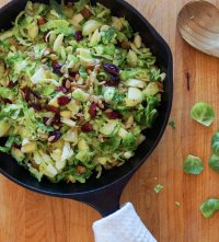 A small cast Iron skillet filled with Brussels sprouts salad and topped with cranberries and extra sunflower seeds.