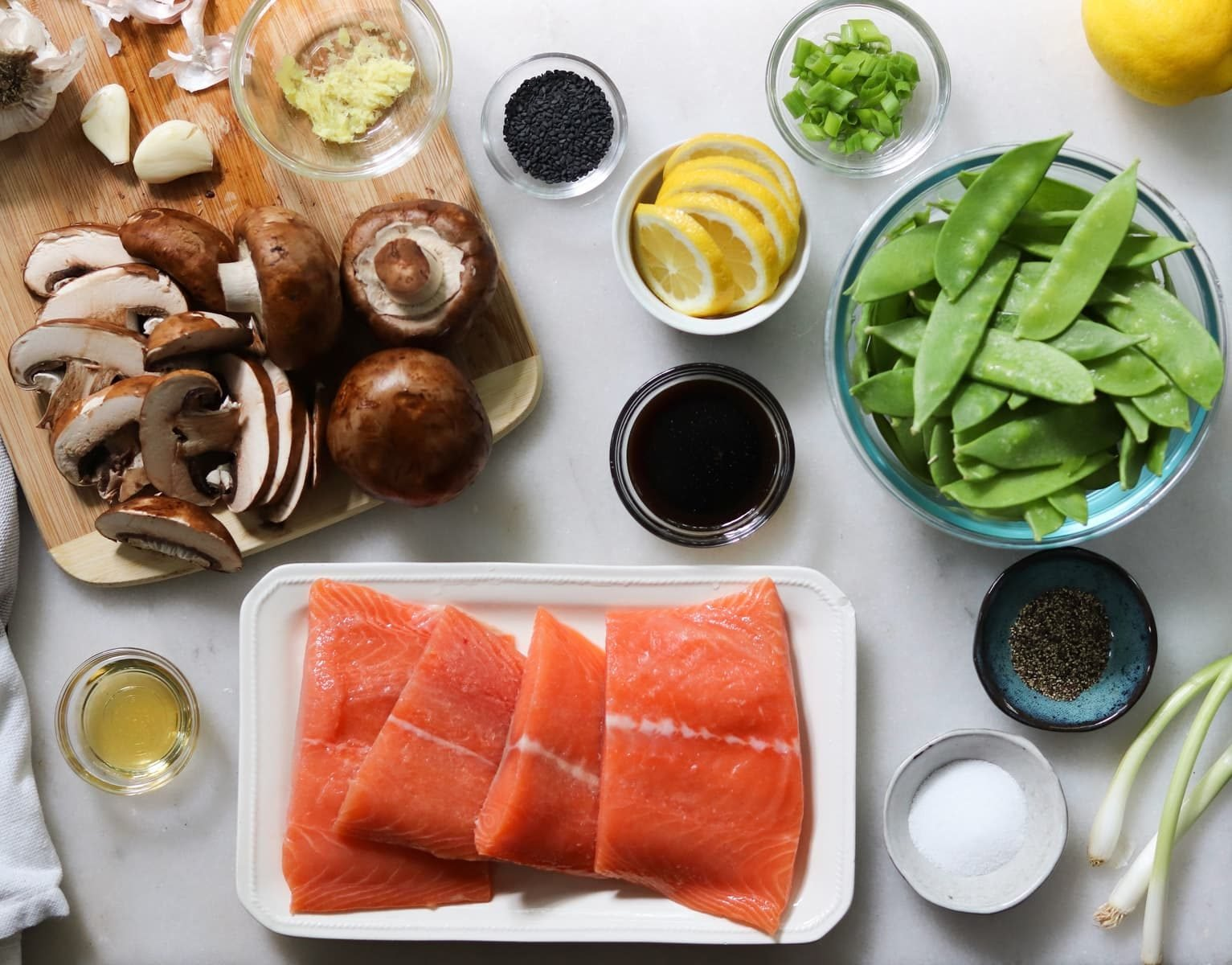 All the recipe ingredients laid out on a white marble board: sliced mushrooms, lemons, green onions, salmon fillets, salt and pepper, sesame oil, coconut aminos, minced ginger, garlic, and snow peas.