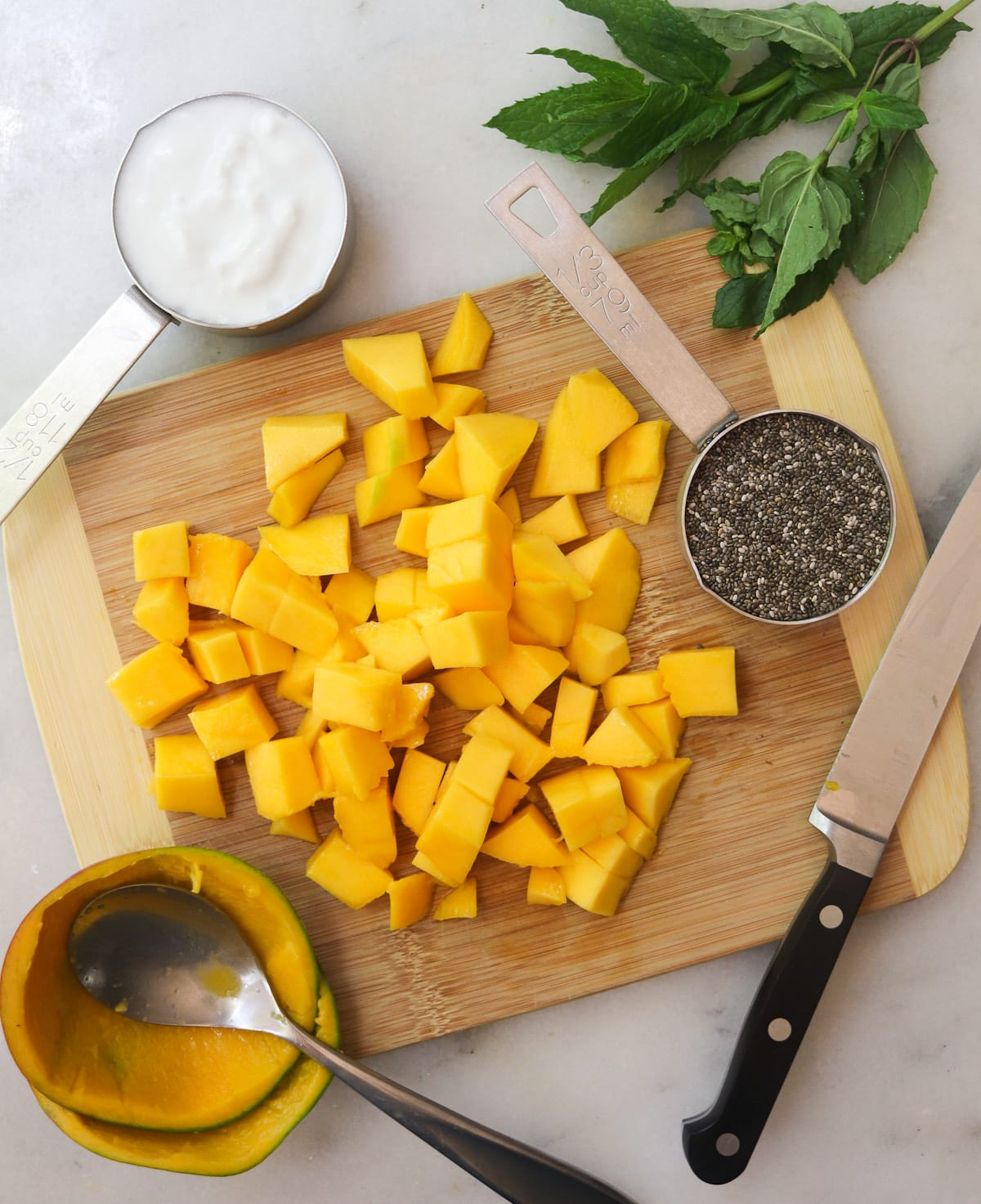Top down of a wooden cutting board topped with diced mango and two small measuring cups filled with coconut milk and chia seeds.