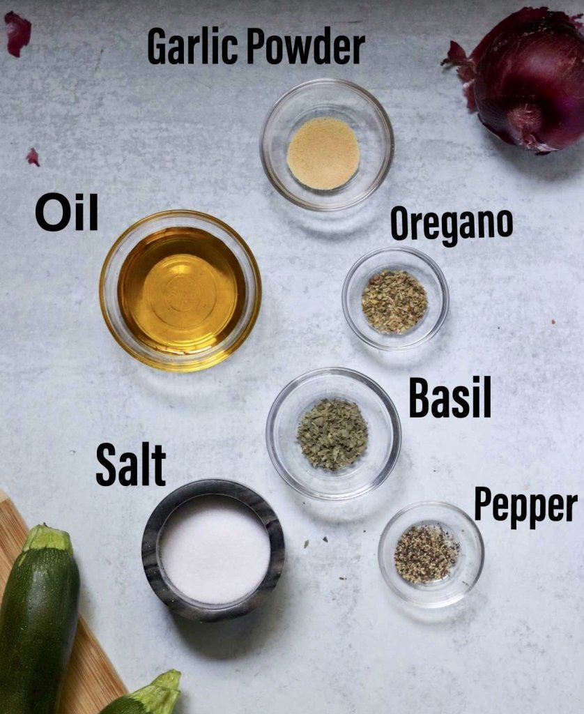 The seasoning ingredients showing individually in small dishes, labeled: garlic powder, oil, oregano, basil, salt, and pepper.