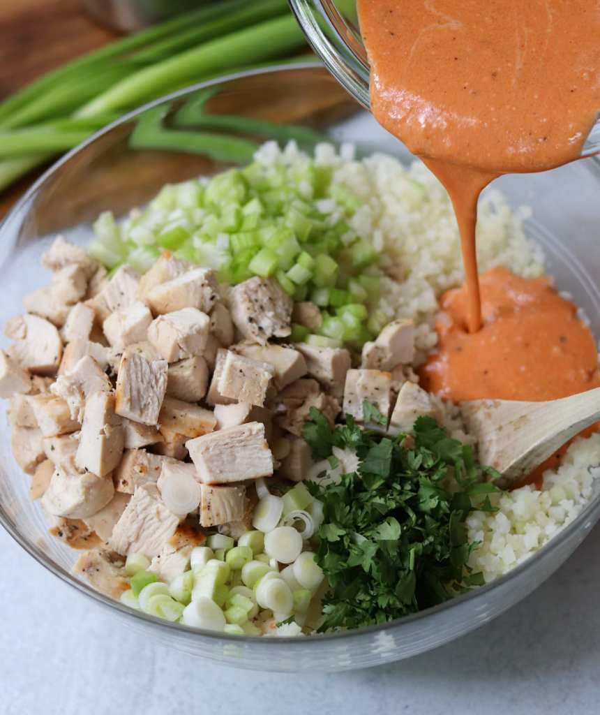 A large glass bowl filled with cauliflower rice, diced chicken, and herbs, with a hand pouring buffalo ranch sauce on top.