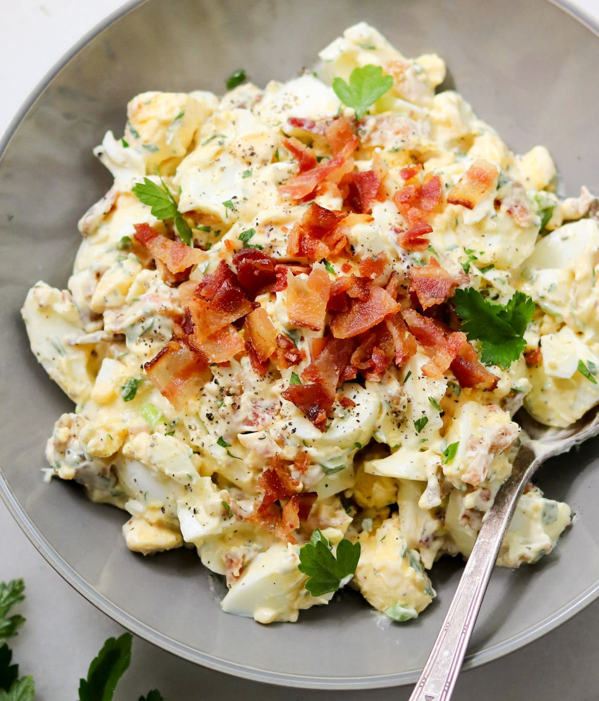 Close up of the finished egg salad in a gray bowl, sprinkled with crumbled bacon and fresh herbs.