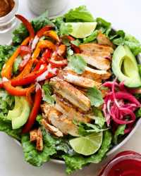A large bowl filled with romaine lettuce, sliced chicken, pickled onions, cooked bell peppers, and garnished with slices of lime and cilantro.