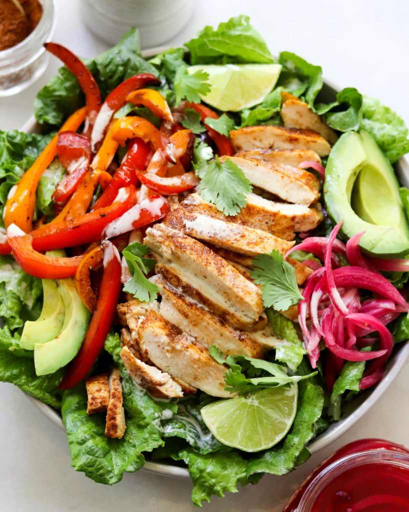 Close up of the finished salad served in a large bowl, filled with romaine lettuce and topped with sliced grilled chicken, bell peppers, pickled onions, sliced avocado, lime, and cilantro.