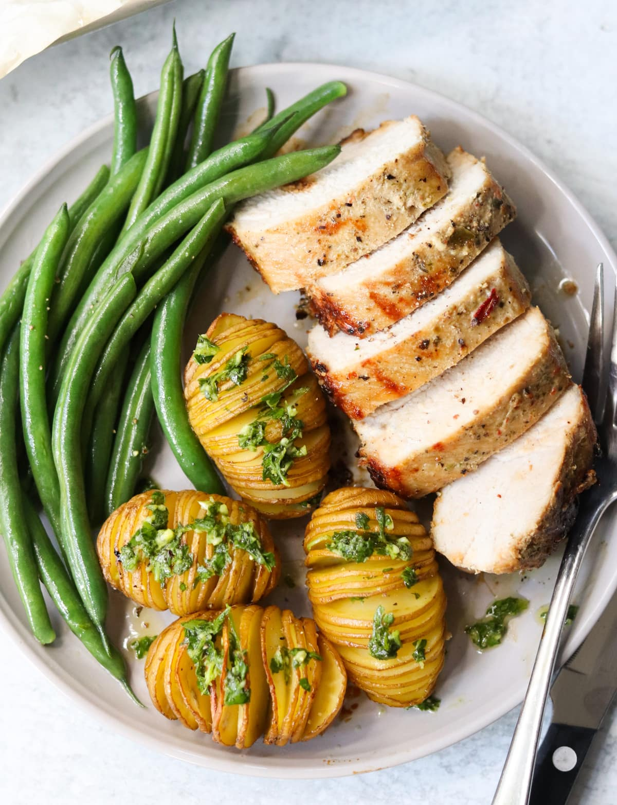 Top down of a small plate with four large slices of cooked pork loin, four small hasselback potatoes topped with green gremolata, and green beans.