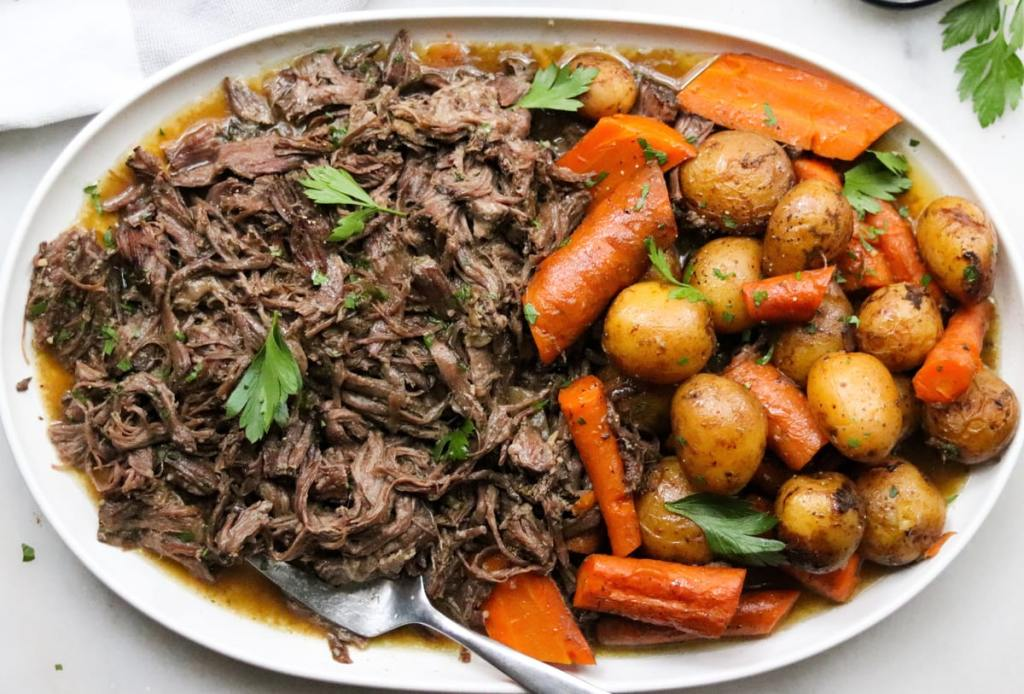 Top down close up of the finished dish filled with shredded beef, vegetables, and gravy on a large white platter, sprinkled with parsley.