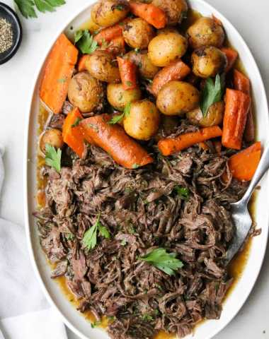 Top down of the shredded pot roast on a large white platter with lots of carrots, potatoes, and gravy.