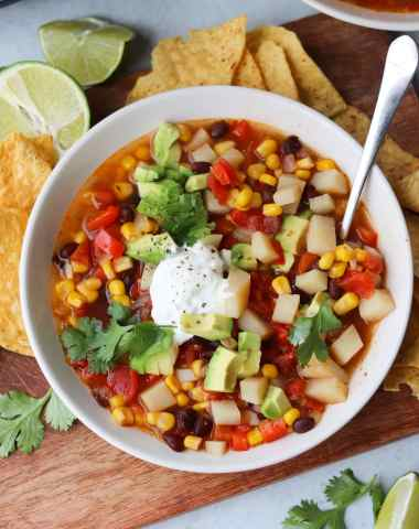 Close up of a bowl of vegetable soup topped with a dollop of sour cream and served with tortilla chips.