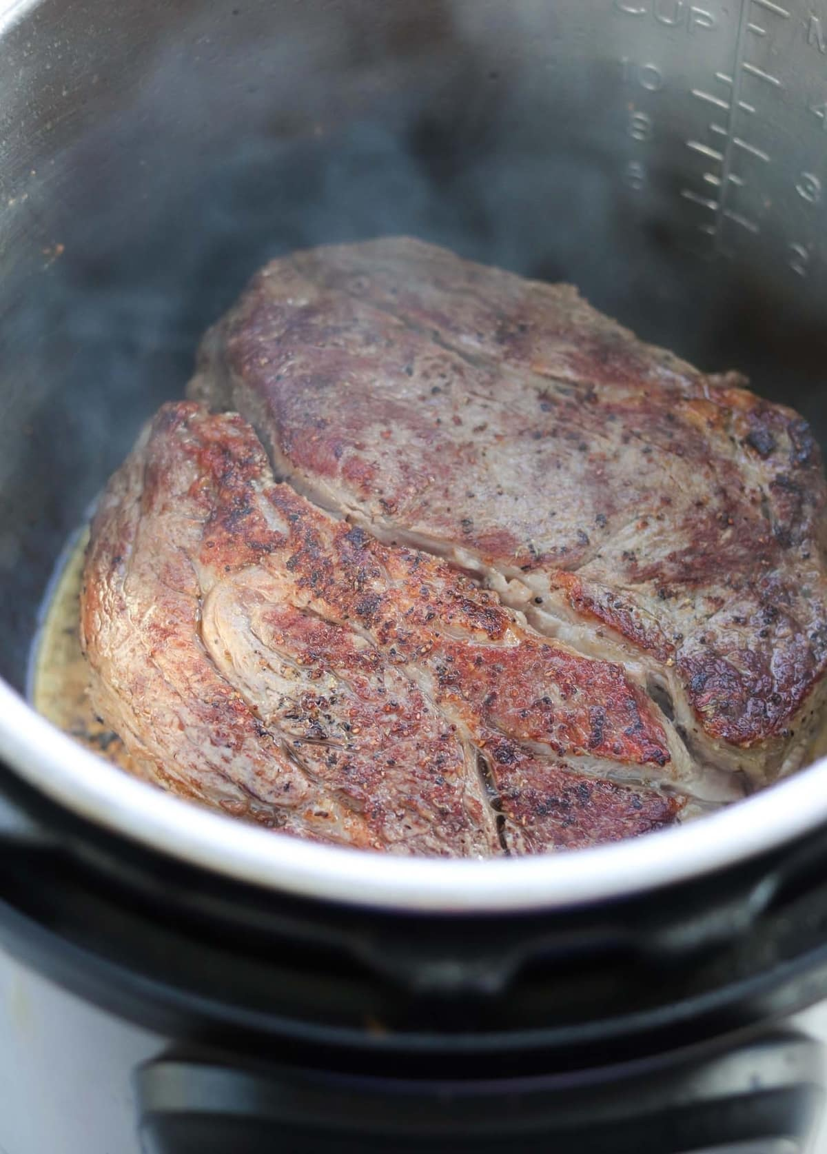 Close up of the seasoned pot roast browning on each side.