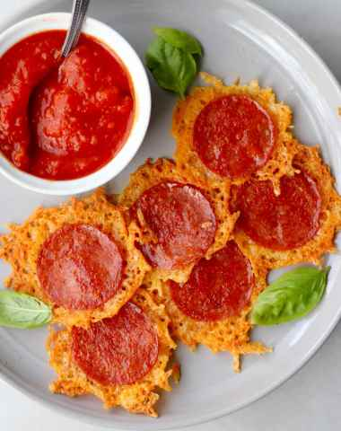 Six pepperoni cheese crisps on a gray plate beside a small dish of tomato sauce.