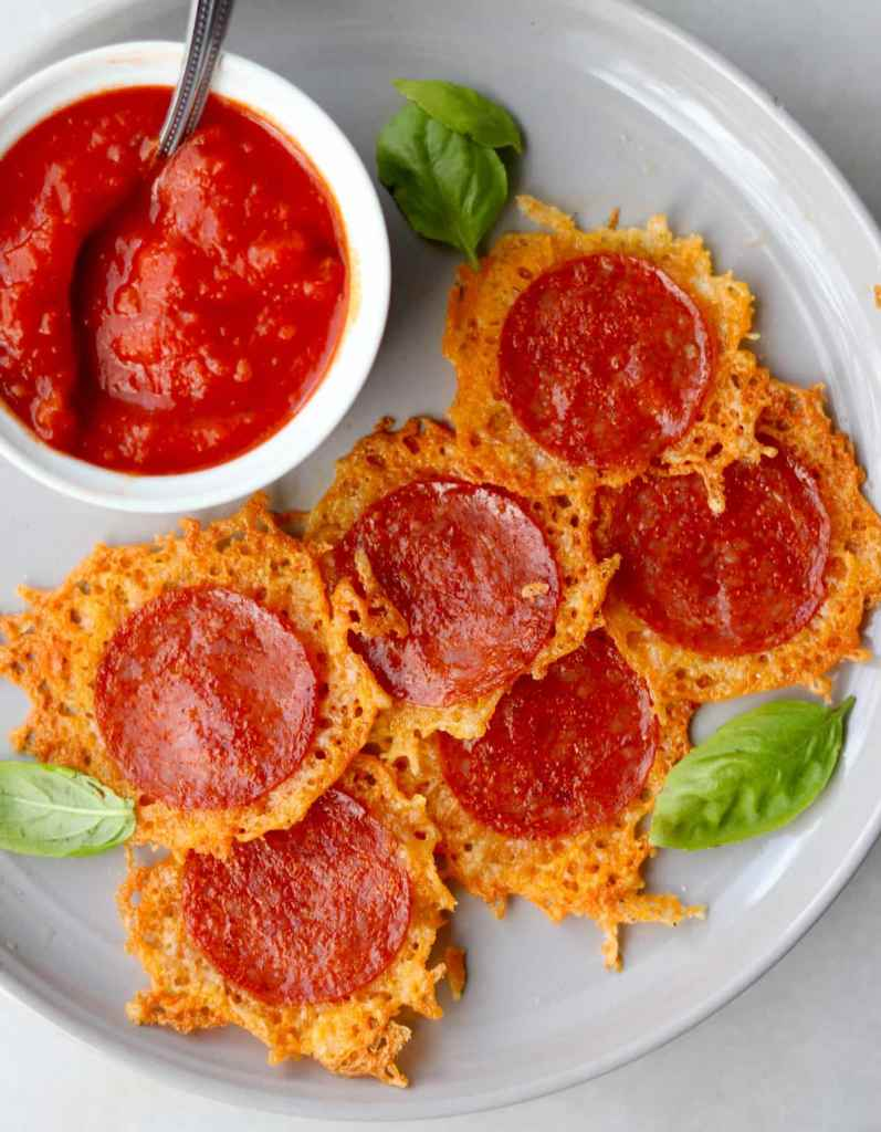 Top down of the plated pepperoni and cheese crisps beside a small dish of tomato sauce.