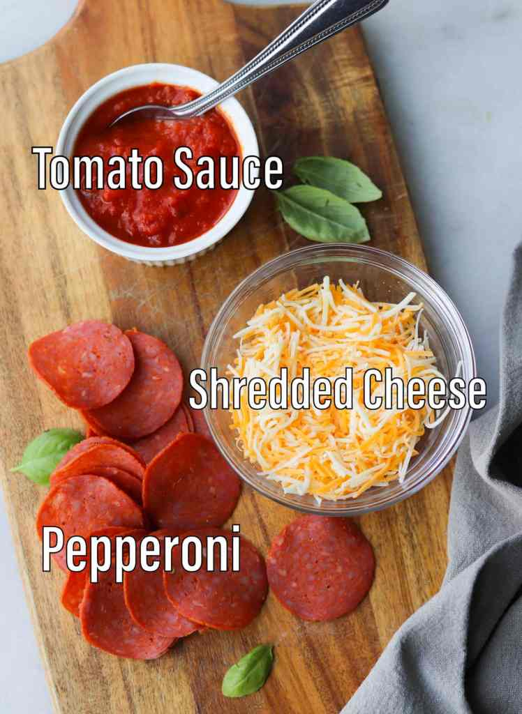 All the recipe ingredients laid out and labeled on a small cutting board: tomato sauce, shredded cheese, and pepperoni.