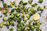 Roasted broccoli florets on a baking pan with a spoonful of nutritional yeast.