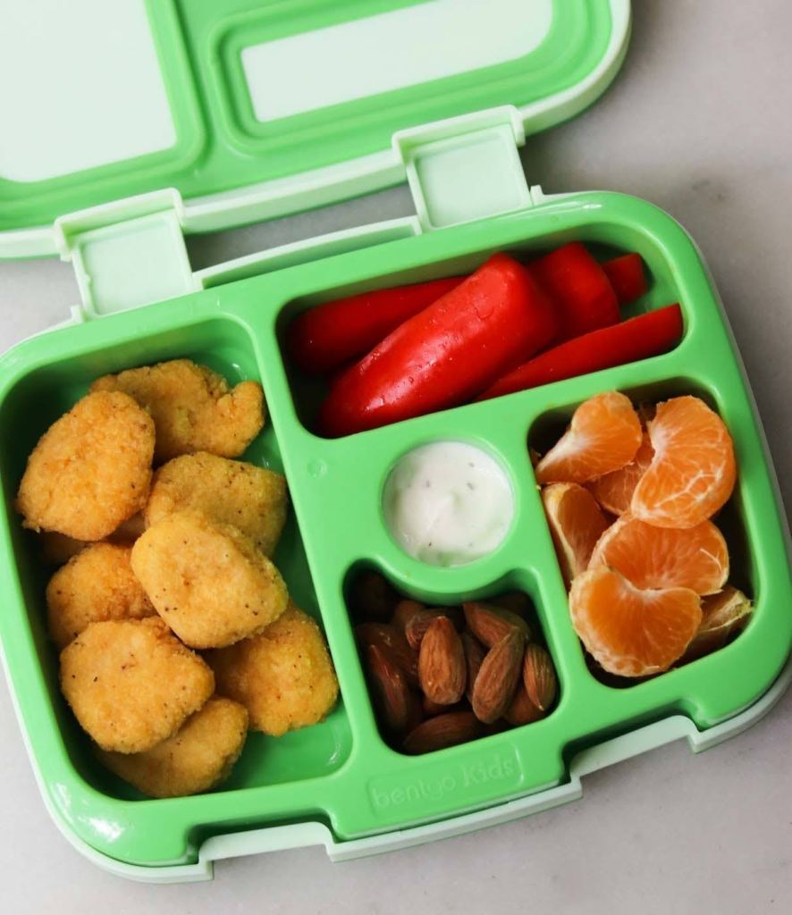 Chicken nuggets, almonds, clementines and sliced baby bell peppers in a green lunch box.