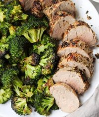 Close up of sliced pork tenderloin on a white plate with roasted broccoli.