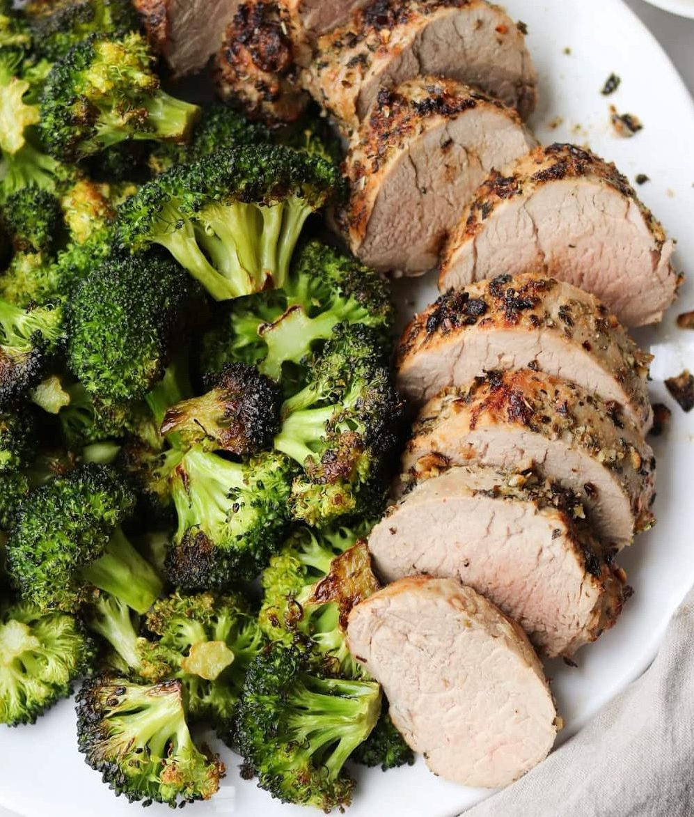 Close up of the cooked air fryer pork tenderloin plated and served with roasted broccoli florets.