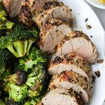 "Close up of the sliced pork tenderloin on a plate with broccoli and the words ""Whole30, Keto Air Fryer Pork Tenderloin"" for Pinterest."