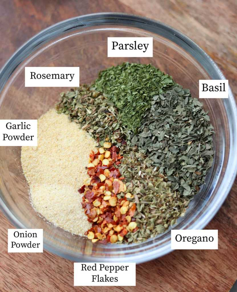 The spices and herbs labeled in a small glass dish: parsley, basil, oregano, red pepper flakes, onion powder, garlic powder, and rosemary.