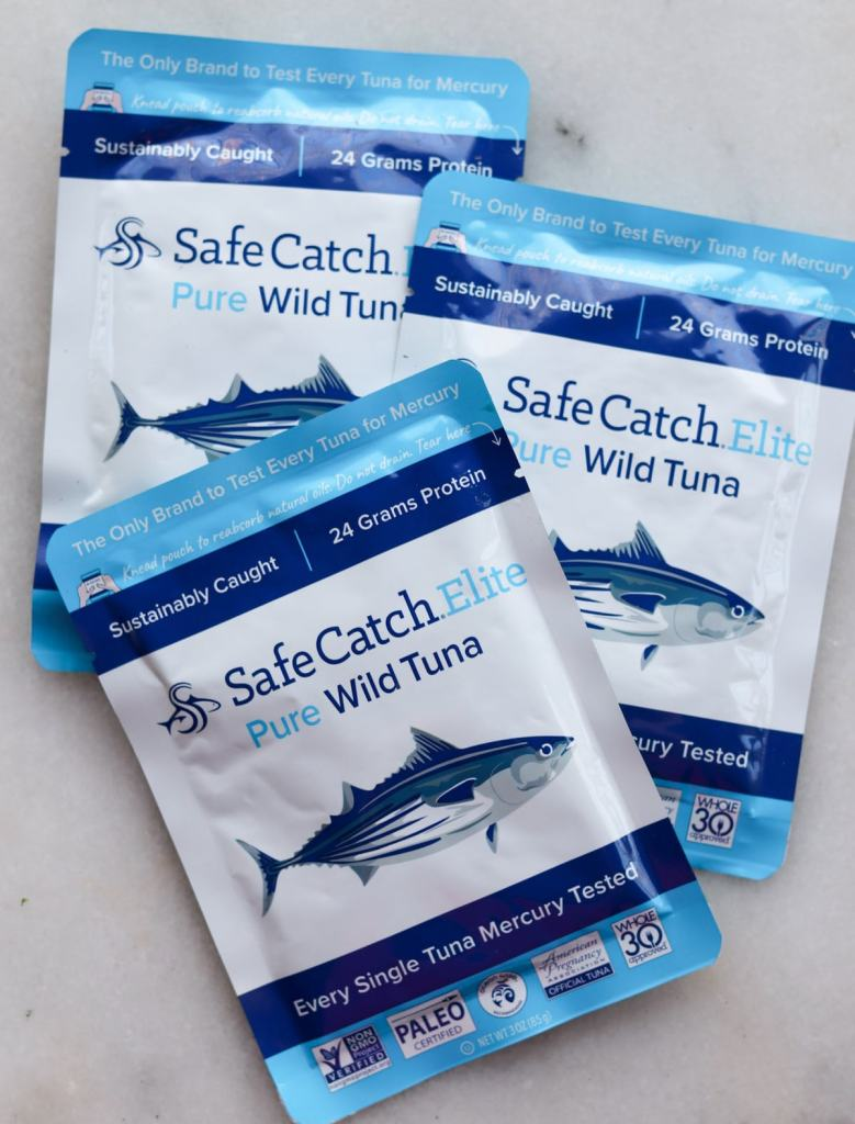 Three bags of safe catch tuna on a white board.