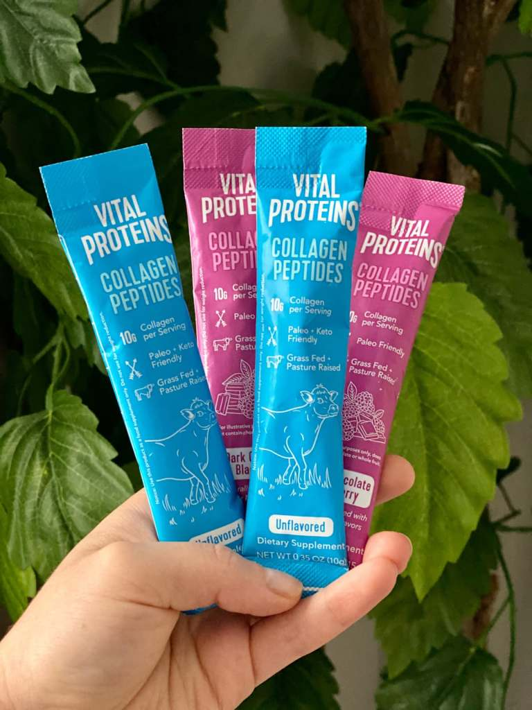 A hand holding blue and purple individual travel packages of Whole30 Approved vital proteins collagens.