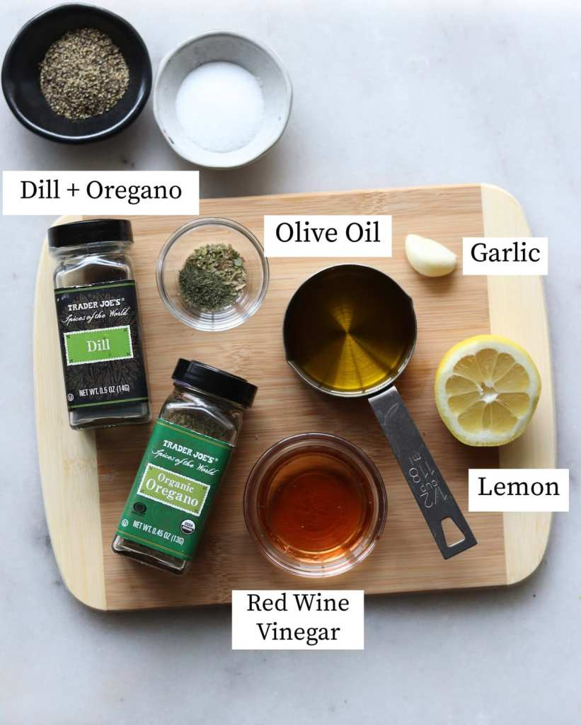All the vinaigrette ingredients laid out and labeled on a wooden cutting board.