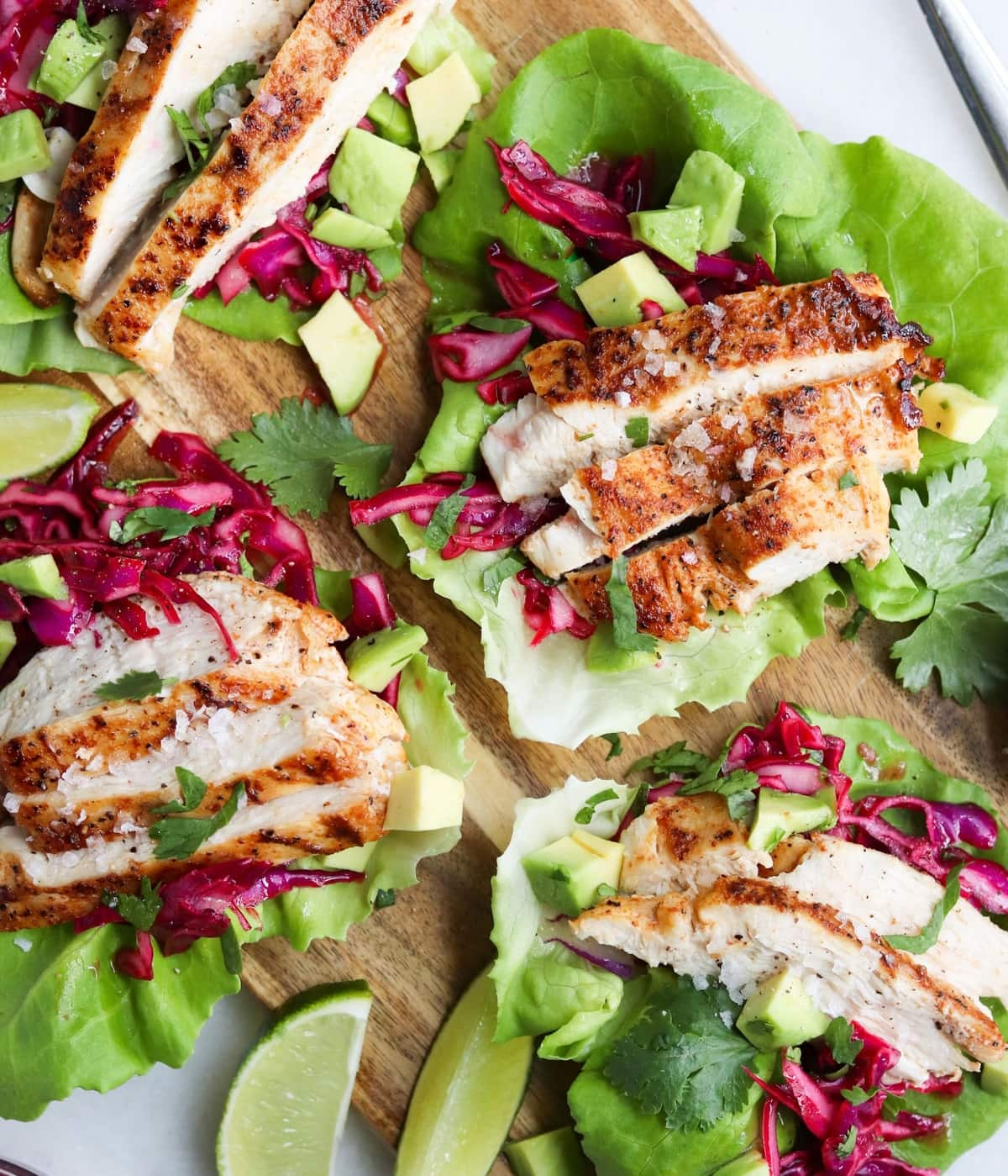 Sliced grilled chicken on lettuce wraps with pickled cabbage.