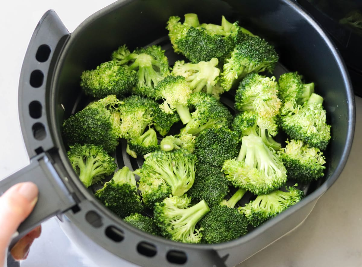The raw seasoned broccoli in the air fryer basket before cooking.