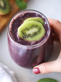 Top down of a hand holding a large glass filled with dark purple kiwi spinach and blueberry smoothie, topped with two slices of kiwi.