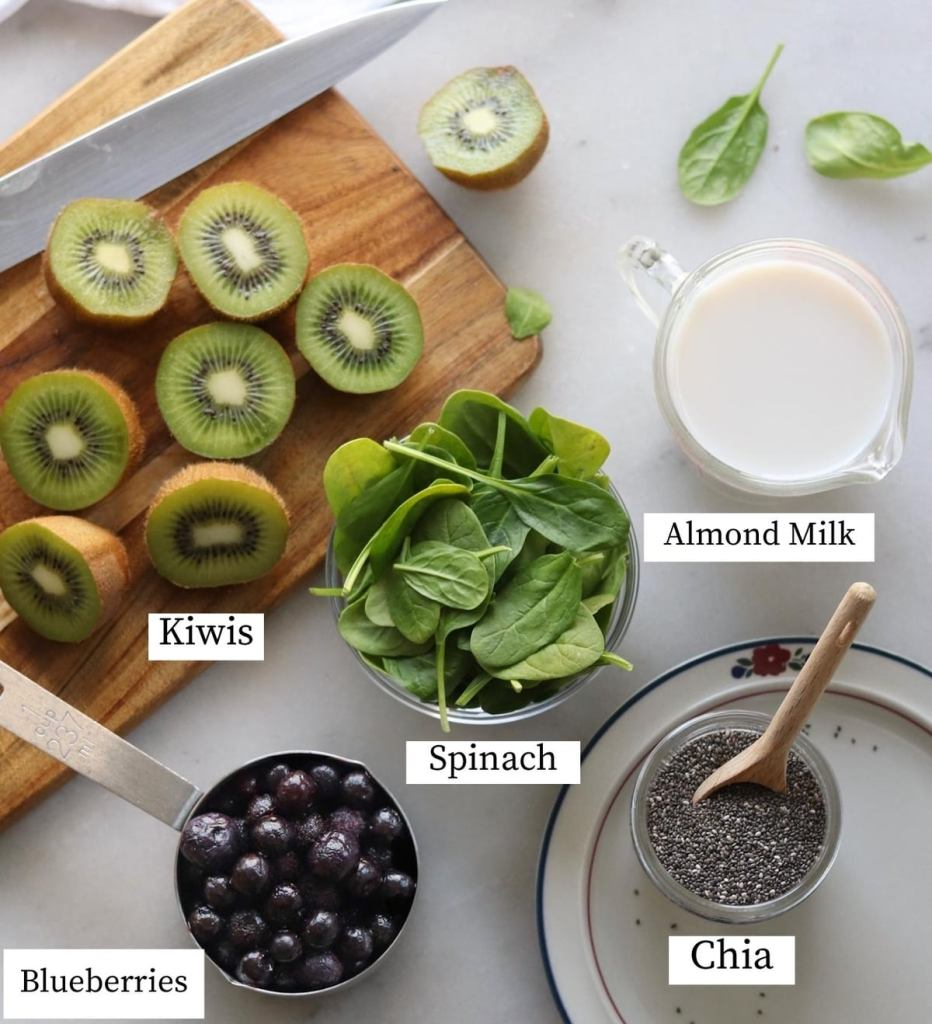All the recipe ingredients labeled on a white marble board: kiwi, almond milk, spinach, blueberries, and chia seeds.