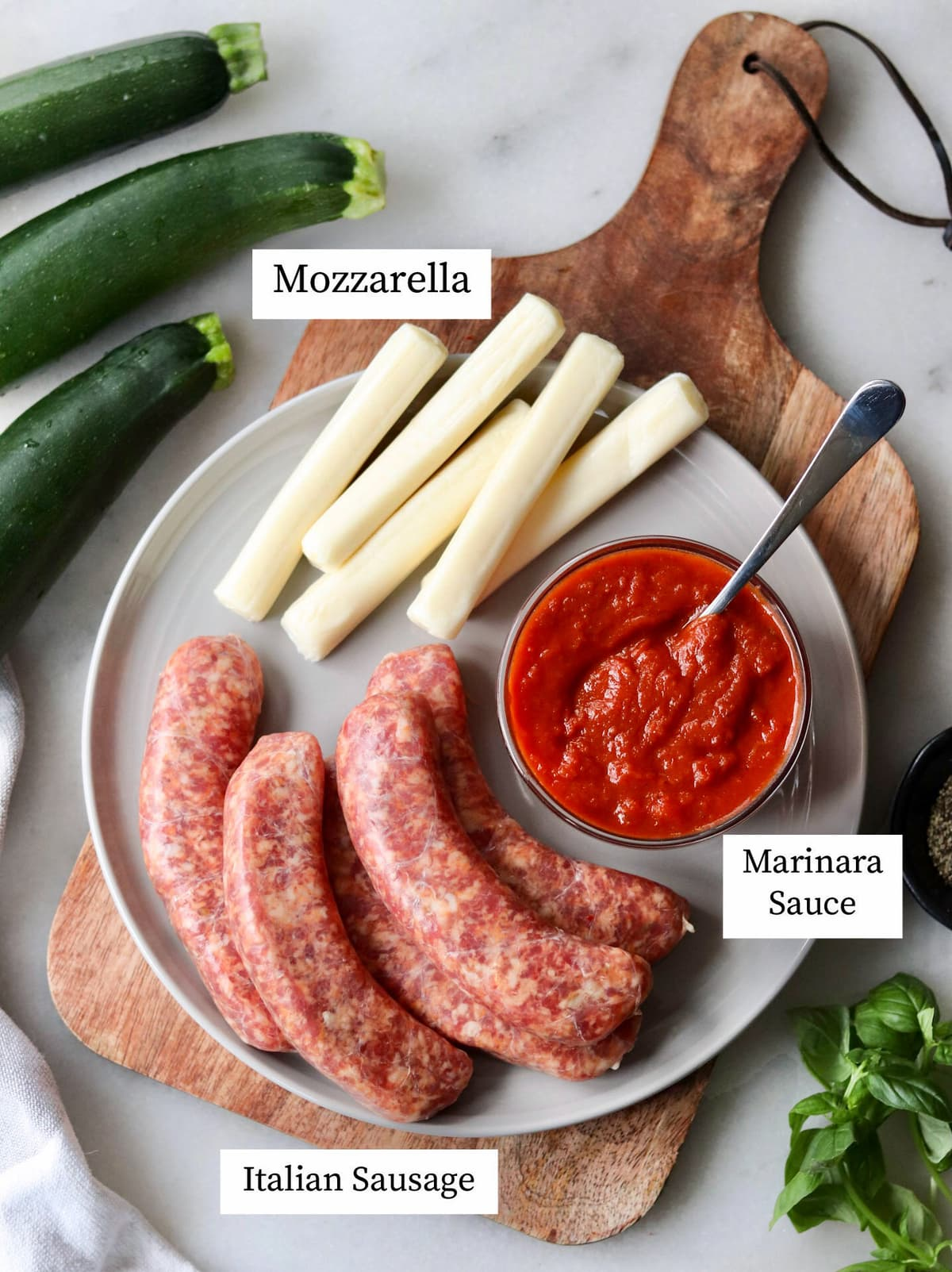 The recipe ingredients laid out on a plate and labeled: mozzarella, Italian sausages, and marinara sauce.