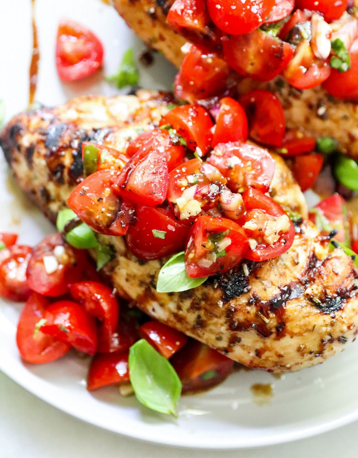 Close up of one plated, cooked chicken breast topped with cherry tomato bruschetta.